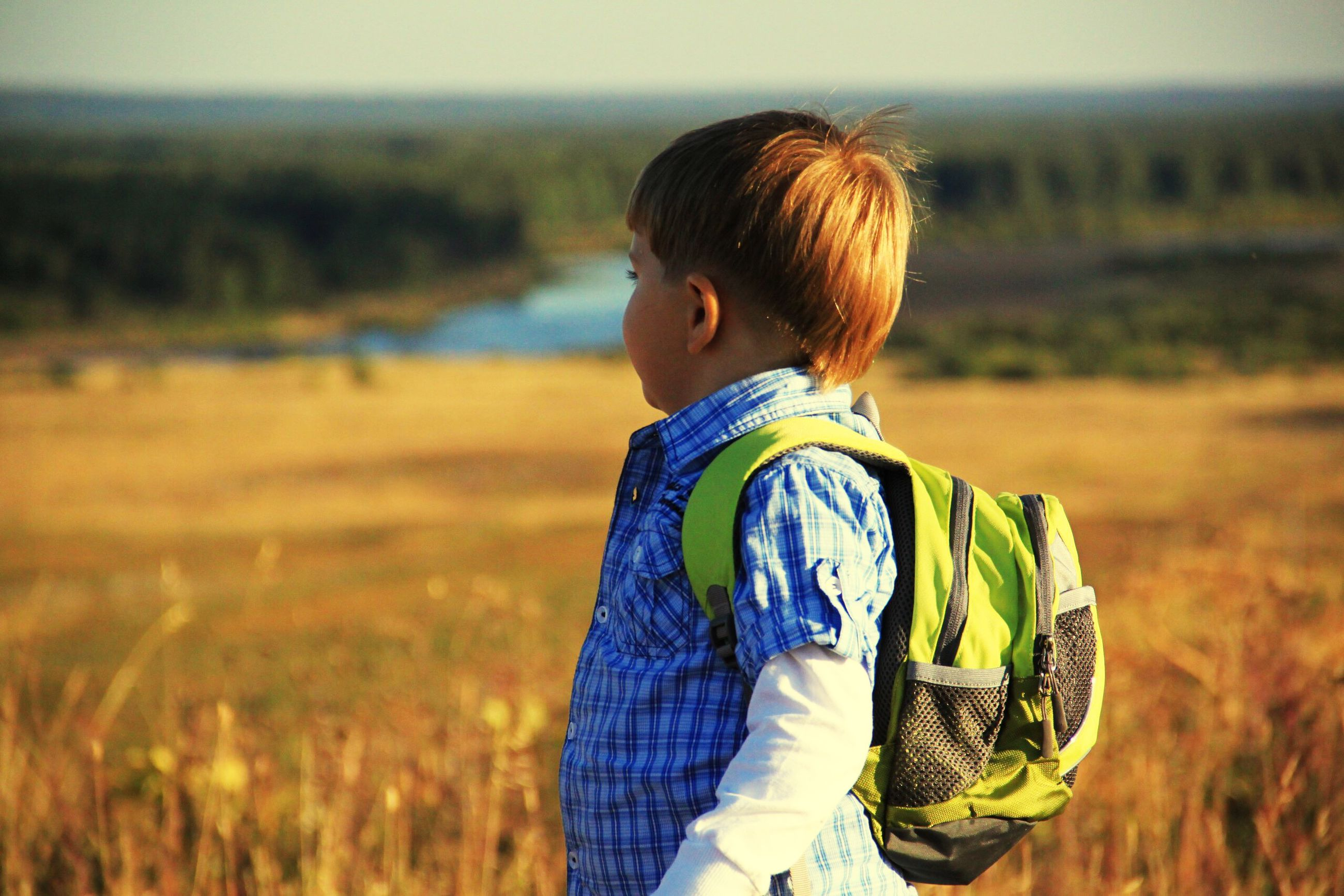 childhood, real people, child, field, one person, leisure activity, land, focus on foreground, lifestyles, nature, rear view, waist up, sunlight, standing, boys, day, casual clothing, women, hairstyle, outdoors, innocence