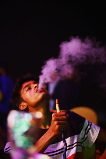 Young man smoking cigarette at night