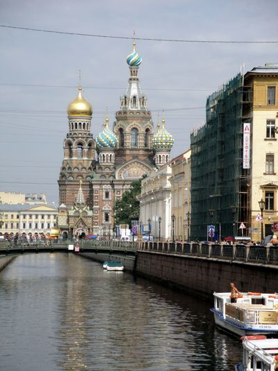 River and church of savior on blood against sky in city
