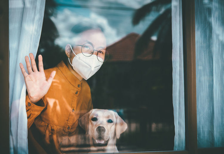 Woman with dog siting by window