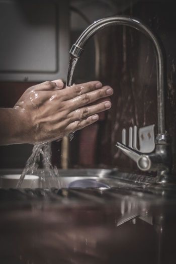 Cropped hand by faucet in kitchen
