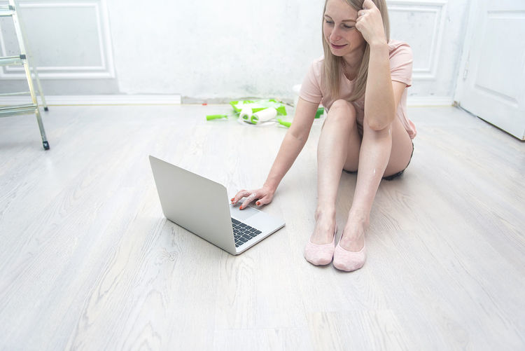Midsection of woman using phone while sitting on wooden floor