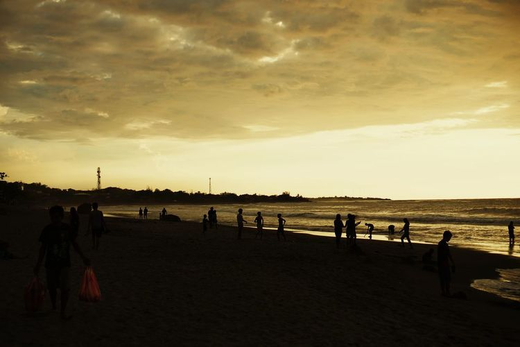 People on beach against sky during sunset