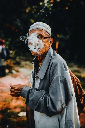 Man exhaling smoke while standing outdoors