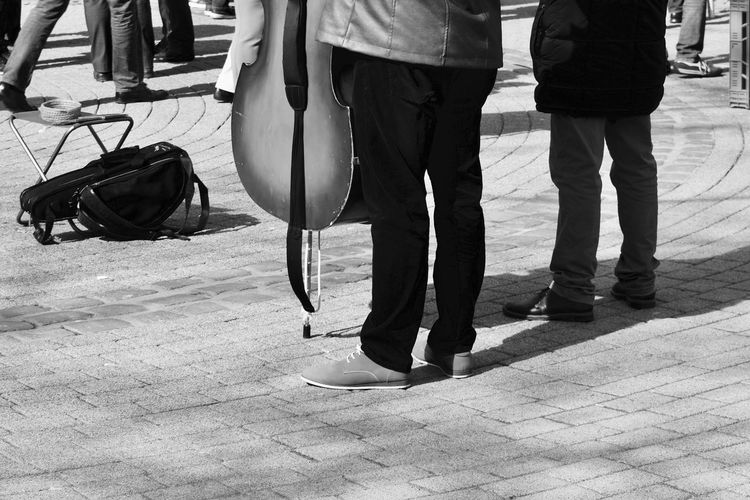 Low Section Of Performer Standing With Musical Instrument On Street