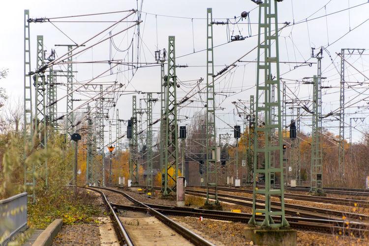 Railroad Tracks Amidst Power Lines Against Sky