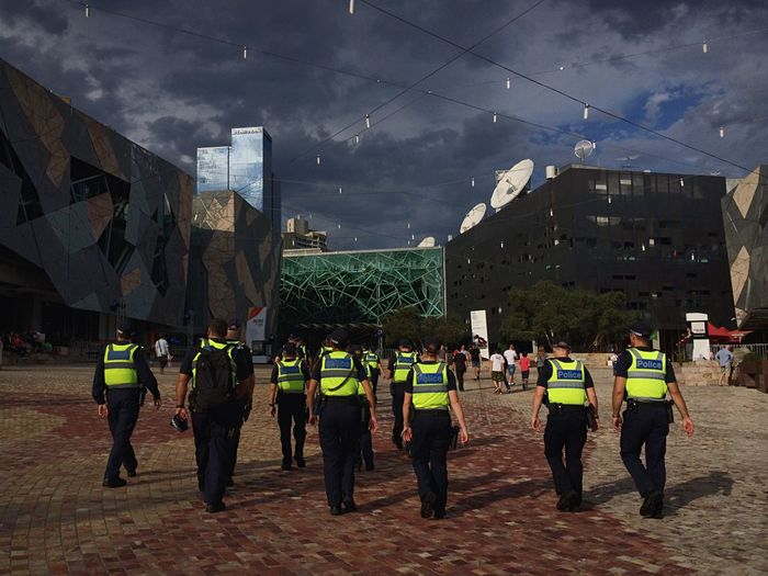 Rear view of policemen walking at federation square against cloudy sky at dusk