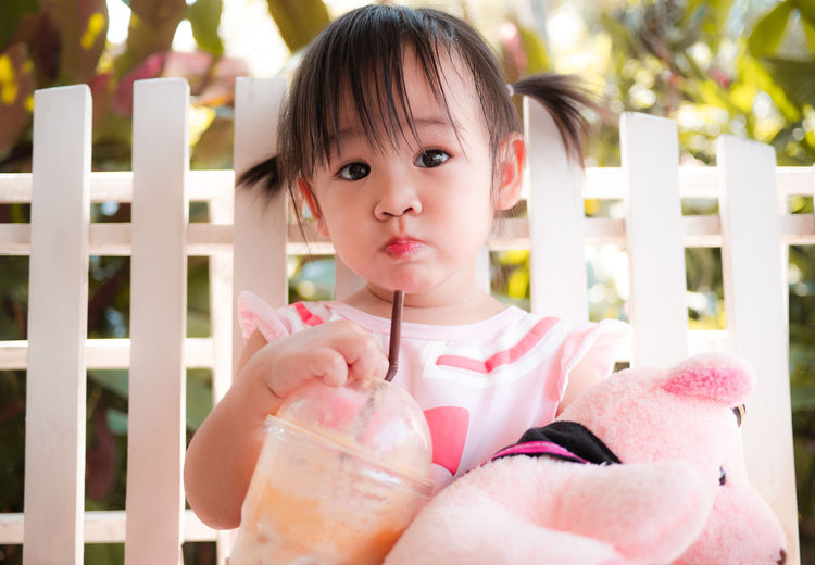 Portrait of cute baby girl drinking smoothie against fence