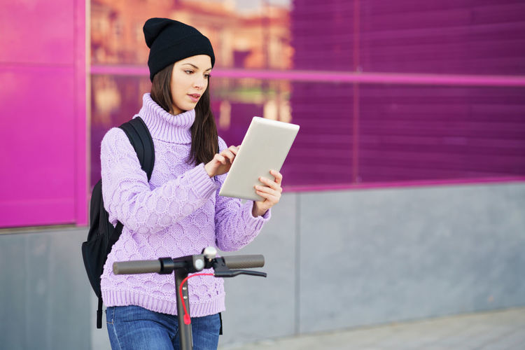 Woman holding smart phone while standing against pink wall