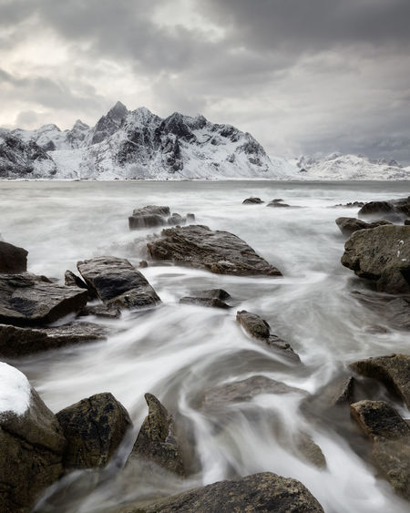 Coastal landscape in winter with water movement between big stones, in the background a mountain range with snow - Location: Norway, Lofoten Winter Scene Winter Landscape Beauty In Nature Cloud - Sky Cold Temperature Day Long Exposure Motion Mountain Mountains Background Nature No People Outdoors Rock - Object Scenics Sea Seascape Seaside Snow Stone Beach Tranquil Scene Tranquility Water Wave Motion Winter