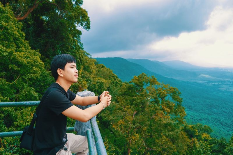 Side view of young man looking at mountain