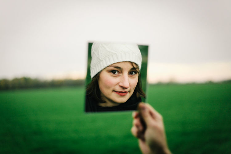 Mirror Adult Body Part Casual Clothing Child Day Front View Grass Green Color Happiness Headshot Holding Human Body Part Human Face Looking At Camera One Person Outdoors Pic In Pic Portrait Selective Focus White Cap Woman Winter Cap Women Young Adult