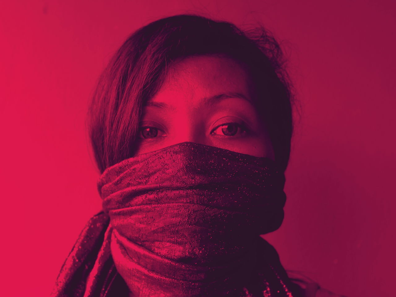 Close-up portrait of young woman covered with scarf against red background