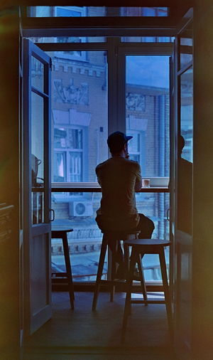 Guy seats on the balcony of cafe Man Morning Sun Morning Coffee SLR Camera Ukraine Balcony Barchair Cafe Kyiv Leasure Weekend Activities