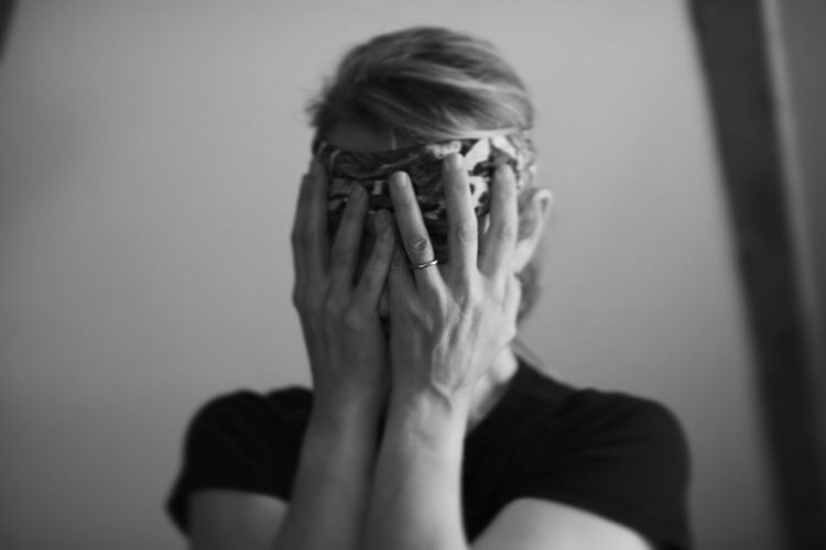 Close-up of woman covering face with hands at home