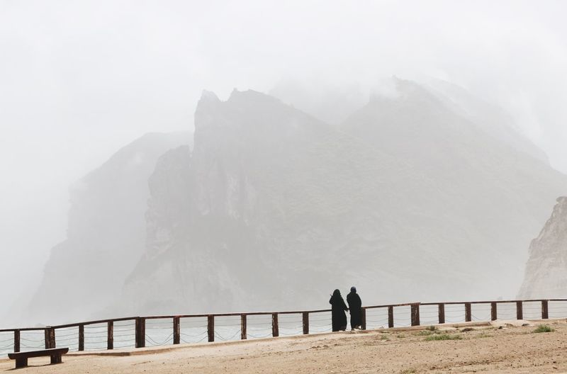 Two arabic women walking on the shore. foggy mountains in background. mughsayl / mughsail in oman.