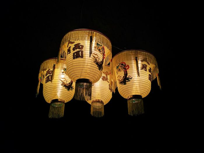 Low angle view of illuminated lantern hanging against black background