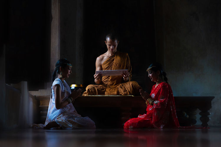 Monk with women praying in temple