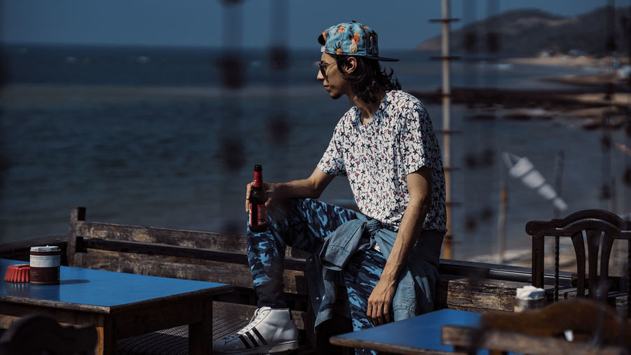 Young man holding beer bottle while looking at sea
