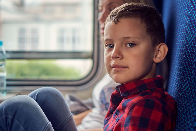 Portrait of cute boy sitting in train