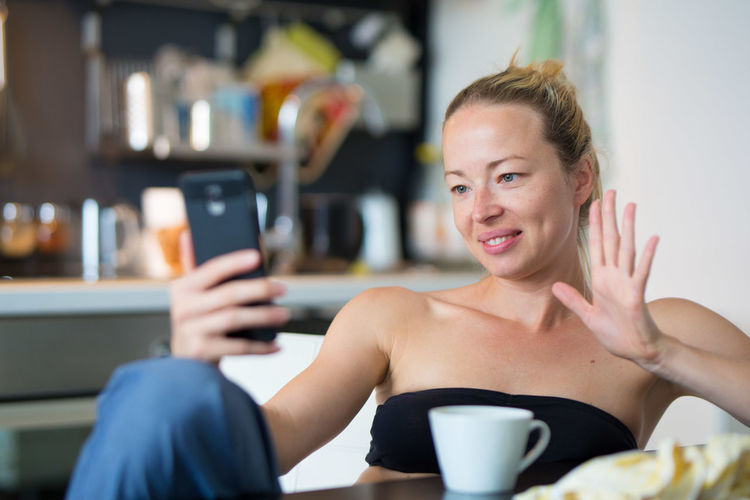 Smiling woman talking on video call sitting at home