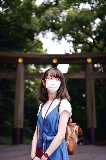 Portrait of girl standing against trees