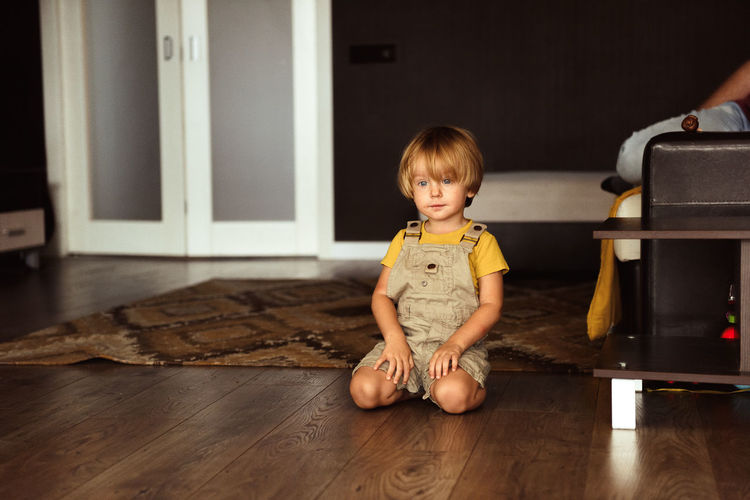 Cute boy sitting on hardwood floor at home