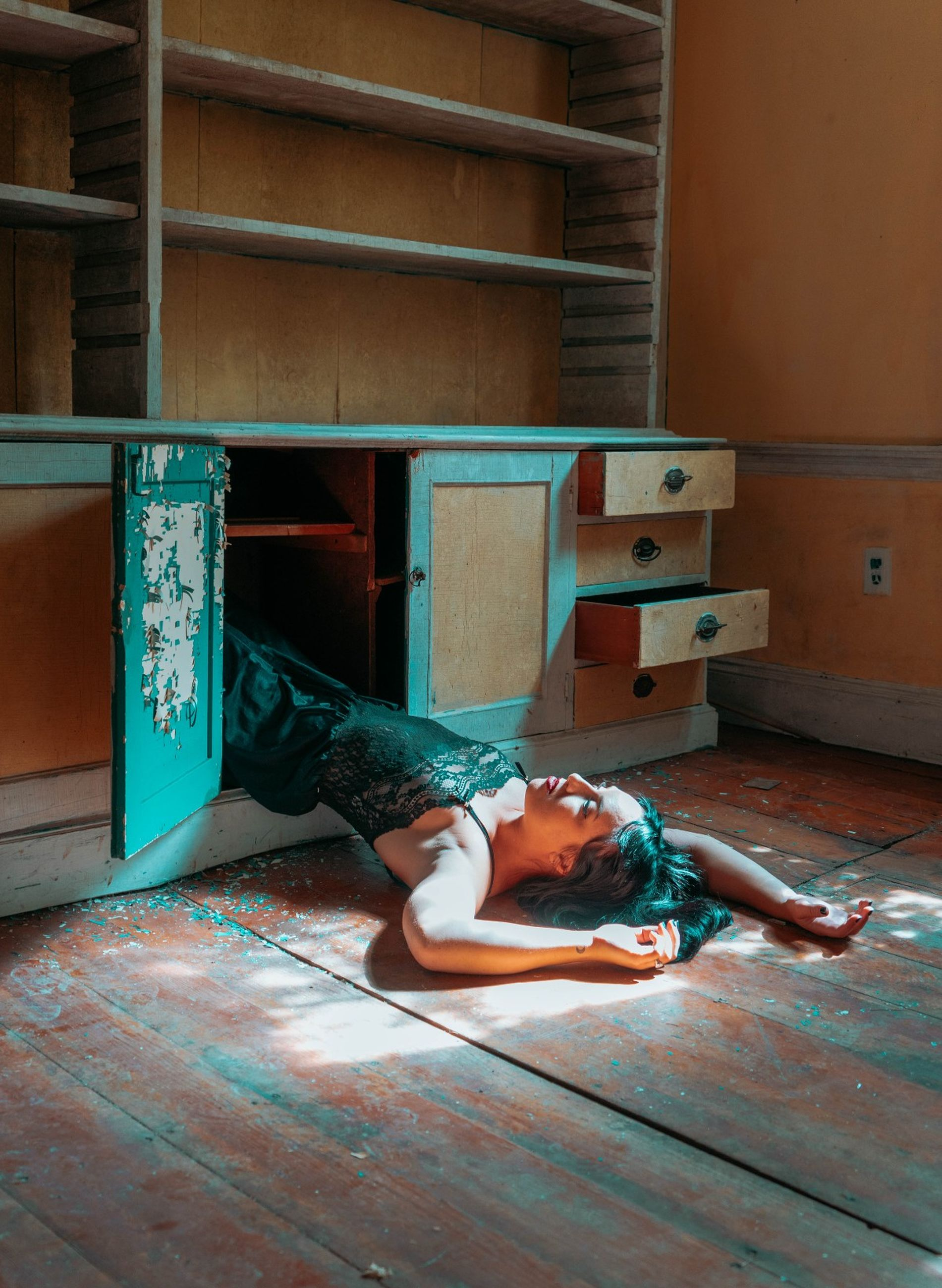 one person, lying down, indoors, full length, real people, relaxation, flooring, lifestyles, home interior, casual clothing, day, resting, young adult, sleeping, leisure activity, window, wood - material, wood, abandoned, hairstyle