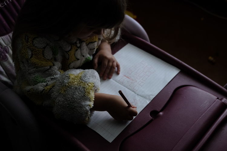 High angle view of girl writing on book at home