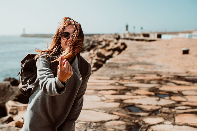 Portrait of woman gesturing while standing on pier over sea