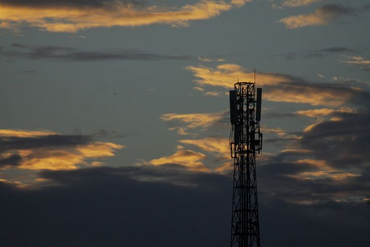 Low angle view of communications tower against sky at sunset