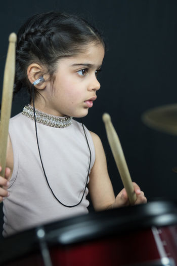 5 year old girl practices on her drums with hearing protection. Arts Culture And Entertainment Casual Clothing Child Childhood Contemplation Front View Girl Girls Hairstyle Holding Indoors  Leisure Activity Lifestyles Looking Music Musical Equipment Musical Instrument One Person Real People School Age Teenager Waist Up Women Young Adult