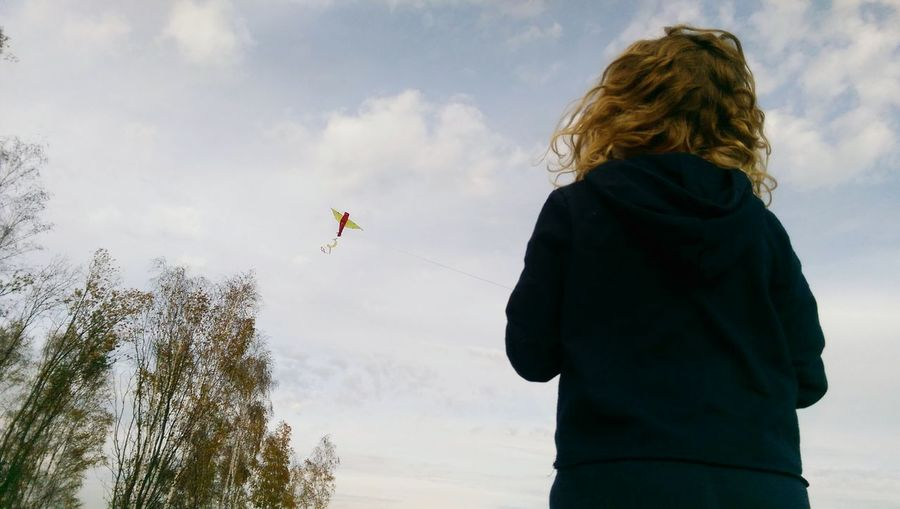 Rear view of woman flying kite while standing against cloudy sky
