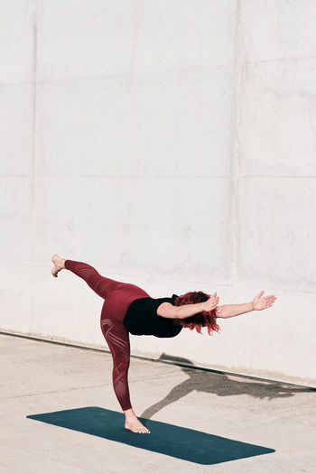 Full length of woman with arms raised against wall
