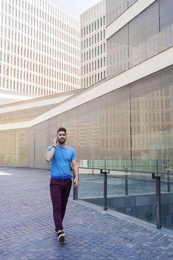 Full length of man running against building in city