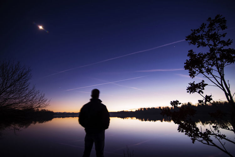 Rear View Of Silhouette Man Standing By Lake Against Sky At Night