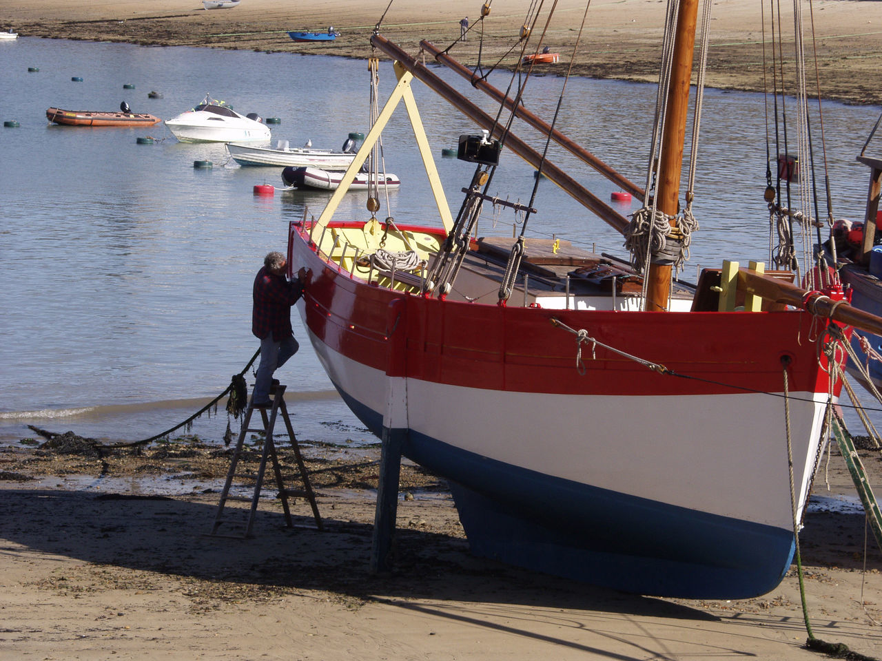 nautical vessel, transportation, mode of transport, sea, water, boat, full length, men, real people, day, nature, one person, moored, outdoors, occupation, standing, working, beauty in nature, beach, one man only, sky, people