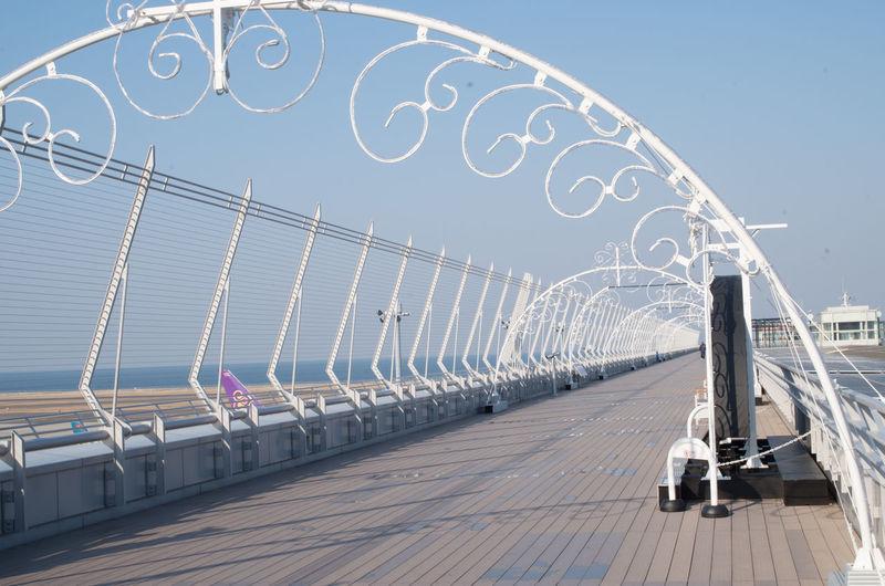 Ferris wheel by bridge against clear sky