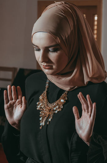 Close-up of young woman wearing hijab praying indoors