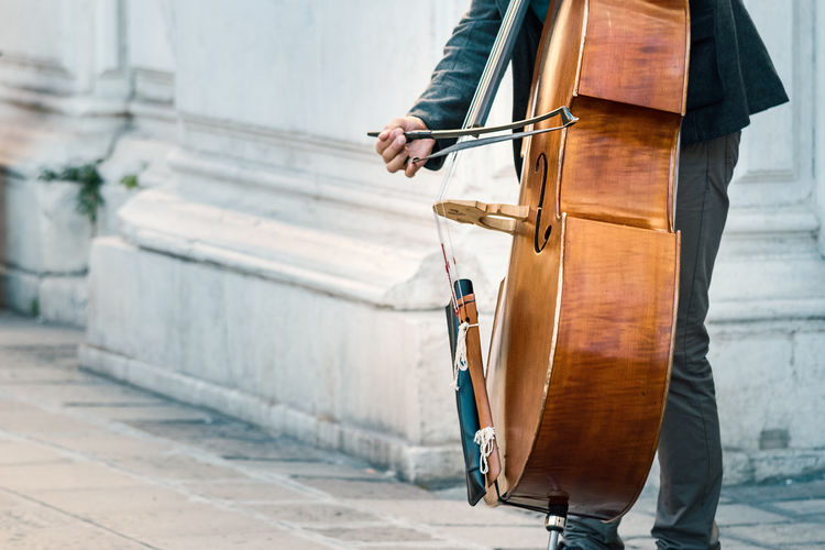 Midsection Of Man Playing Cello On Footpath In City