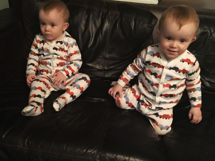 Twin brothers sitting on sofa at home