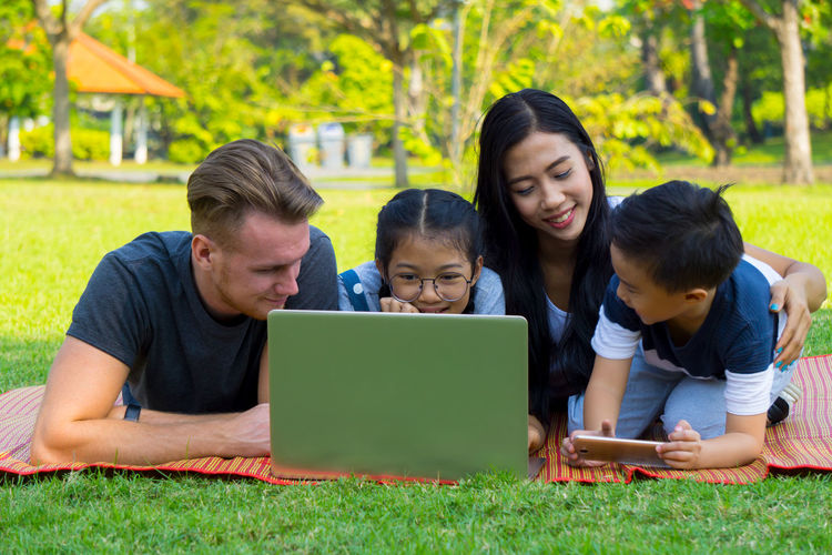 Happy family using laptop at park