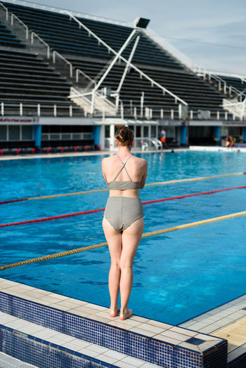 Rear view of woman standing at poolside