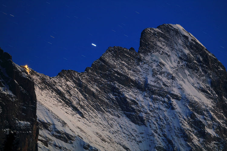 Low angle view of snowcapped eiger against clear sky at dusk