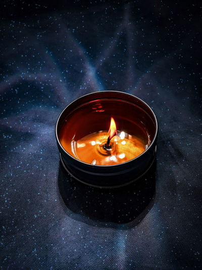 High angle view of lit candle on table