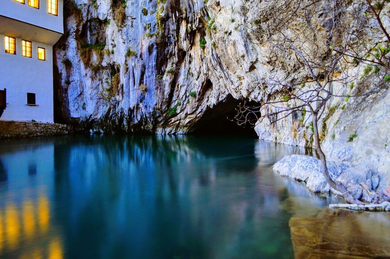 Scenic view of cave by water