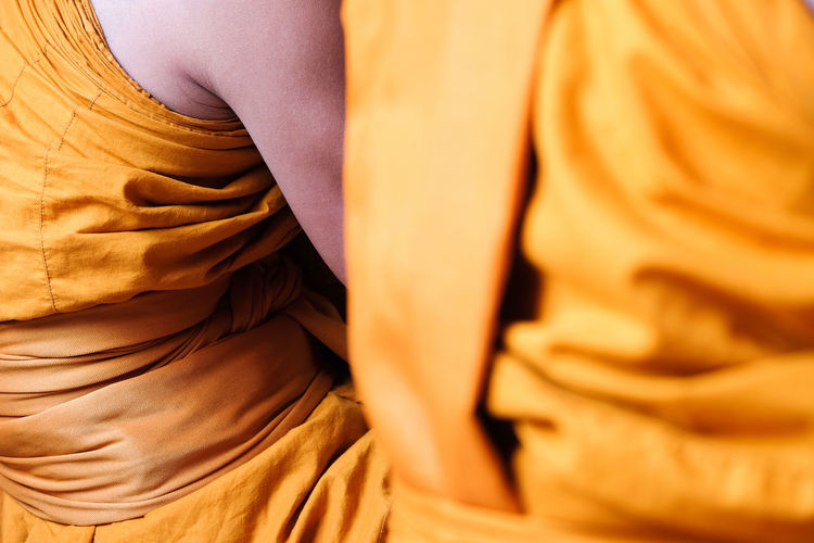 Midsection of monks wearing traditional clothing while sitting in temple
