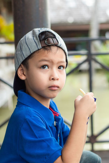 Boy looking away while sitting against railing