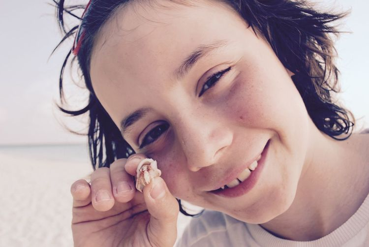 Close-up portrait of smiling girl holding hermit crab