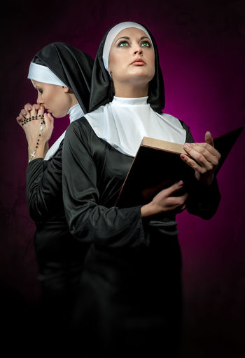 Young Nuns With Bible And Rosary Beads Standing Against Colored Background